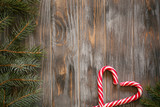 festive cozy christmassy atmosphere. minimalistic holiday decor. fir tree branch and candy cane in heart shape on wooden background. - 222030543