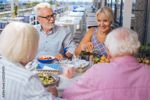 Poster Perfect mood. Delighted elderly people talking to each other while enjoying their meal together
