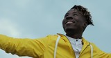 African man in yellow jacket enjoy weather overcast cloudy sky with raised hands - 222034943