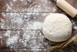 Raw dough with rolling pin and wheat ears on brown wooden table