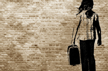 Graffiti/shadow on a brickwall showing a refugee girl walking with her suitcase © bettysphotos