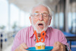 Joyful mood. Portrait of a nice aged man blowing at the candles while celebrating his birthday