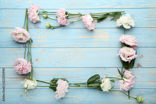 Beautiful eustoma flowers on blue wooden table - 222036948