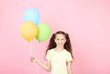 Cute young girl with colored balloons on pink background - 222037306