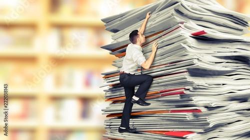 Leinwandbild Motiv Businessmen climbing up a pile of documents on backround