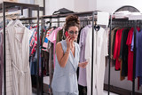 Listen attentively. Concentrated female showroom owner staying in store and using phone - 222038520
