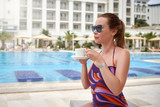 Young European lady is sitting at the sunbed near the pool. She is enjoying her holidays and holding a cup of coffee in her hands. - 222038966