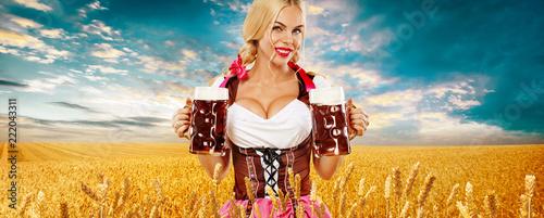 Leinwandbild Motiv Beer party. Sexy Oktoberfest woman - waitress, in Munich wearing a traditional german Bavarian dress, serving big beer mugs on golden wheat field background.