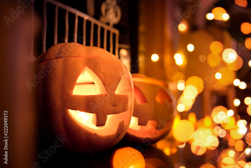 Halloween pumpkins at home on a fireplace with sparkling lights. Cosy autumn background.