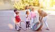 Kinder machen Sport auf Schulhof mit Reifen