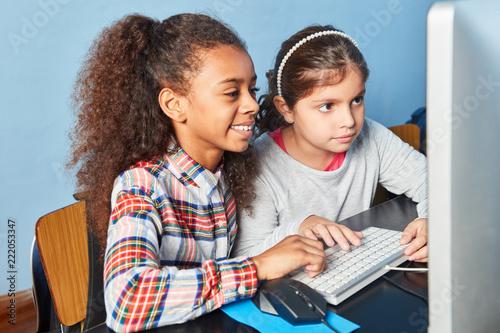 Leinwanddruck Bild Zwei Mädchen zusammen am Computer