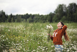 Beautiful girl collects daisies in summer field - 222055571