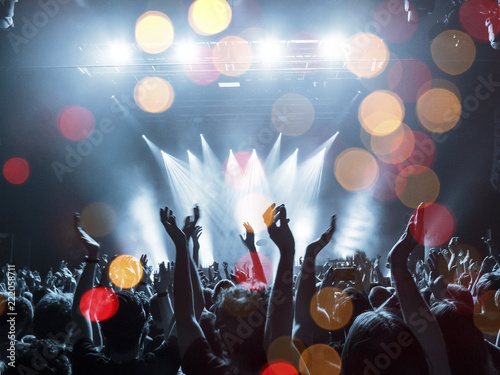 Concert lights over a crowd clapping - 222058711