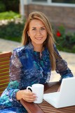Woman using laptop on a patio while holding a coffee mug - 222064797