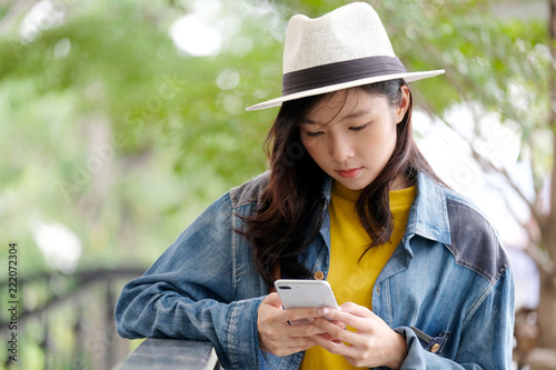Fototapeta Young asian woman using smart phone in city outdoors background, people outdoor with technology, people on phone, lifestyle