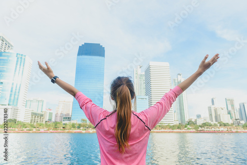 Fototapeta Back shot of young asian woman relax herself and warm down after city running exercise with a city view background and warm light cleared sky late of the afternoon. Outdoor running exercise concept.