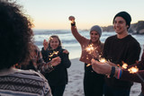 Young people having fun with sparklers at beach