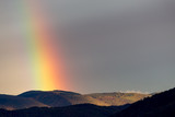 Beautiful and surreal view of part of a rainbow over some hills - 222091734