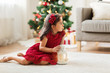 christmas, holidays and childhood concept - little girl with lantern at home