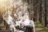 A man in a cassock spends a ritual in a dark forest - 222096323