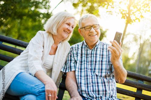 Szczęśliwa starsza para używa smartphone w parku.