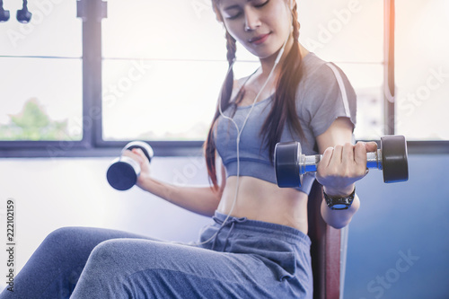 Wall mural Portrait of Fit woman muscular bodybuilder workout with dumbbells in fitness gym.