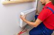 Leinwanddruck Bild - plumbing services - plumber installing heating radiator on the wall