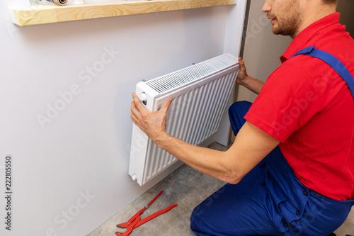 Leinwanddruck Bild plumbing services - plumber installing heating radiator on the wall