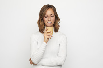 young woman with cup of coffee looks down bites the lip