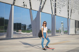A teenage girl with a red penny board in her hands is standing, looking at the camera and smiling. - 222107355