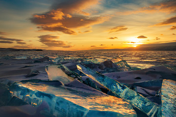 Beautiful colorful sunset over the crystal ice of Baikal lake. Transparent blue Toros Baikal ice is shining through the crack sunset