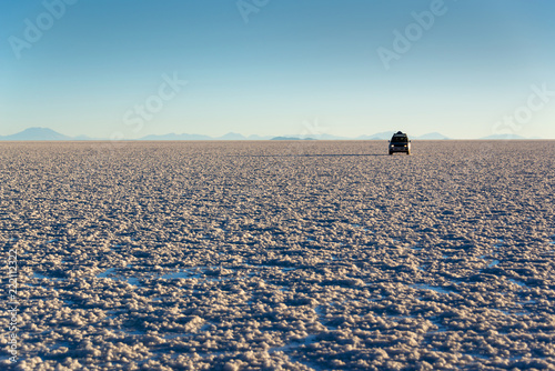 Silhouette of a car in Salar de Uyuni (Uyuni salt flats) at sunset, Potosi, Bolivia