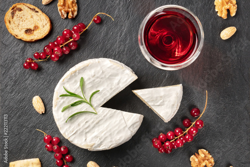 Fototapeta An overhead photo of Camembert cheese with a glass of red wine, fruits and nuts, shot from above on a black background