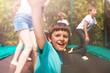 Leinwanddruck Bild - Happy boy jumping on trampoline with his friends