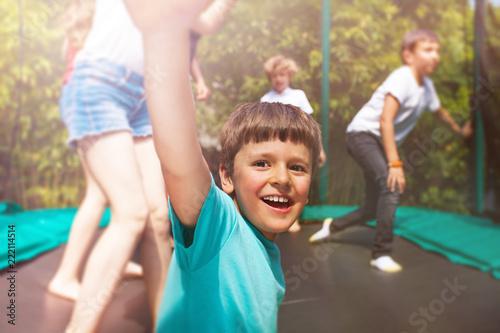 Leinwanddruck Bild Happy boy jumping on trampoline with his friends