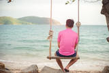 Alone man thinking while swinging on the beach - 222115586