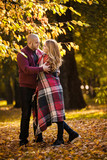 Happy couple go for a walk in autumn park covered in plaid - 222118718