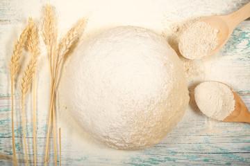 тесто для хлеба колосья пшеницы и мука лежат на столе