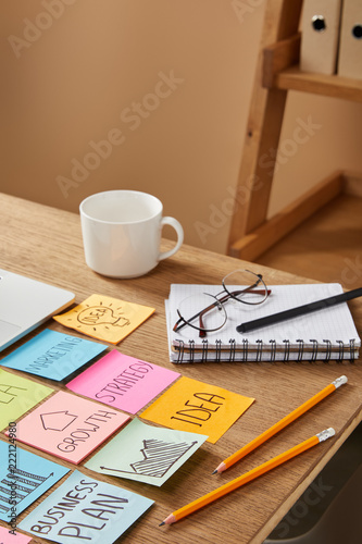 paper stickers with business strategy and cup of coffee on tabletop