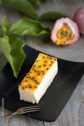 Poster Passion fruits cheese cake slice  on wooden background. Vertical composition
