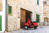 vintage red motor scooter parked on cobbled street in hostoric spanish village