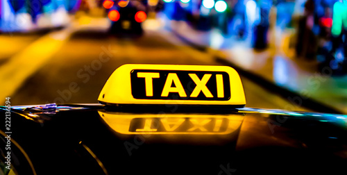 Leinwanddruck Bild Night picture of a taxi car. Taxi sign on the car roof glowing in the dark