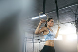 Fitness Woman Training With Gymnastics Rings At Crossfit Gym