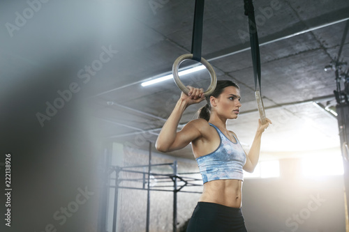 Wall mural Fitness Woman Training With Gymnastics Rings At Crossfit Gym