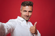 Leinwandbild Motiv Handsome brunette man 30s with stubble in white shirt taking selfie photo and showing thumb up, isolated over red background