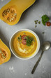 Pumpkin cream soup with parsley, tomatoes and seeds with spoon and towel at gray background - 222144392