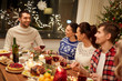 holidays and celebration concept - happy friends having christmas dinner at home and eating