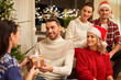 celebration and holidays concept - happy friends with glasses celebrating christmas at home party and giving presents