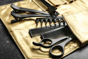 Bag with professional hairdresser's set on black table