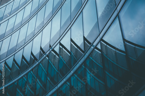Foto Murales Abstract business modern city urban futuristic architecture background. Real estate concept, motion blur, reflection in glass of high rise skyscraper facade, toned blue picture with bokeh